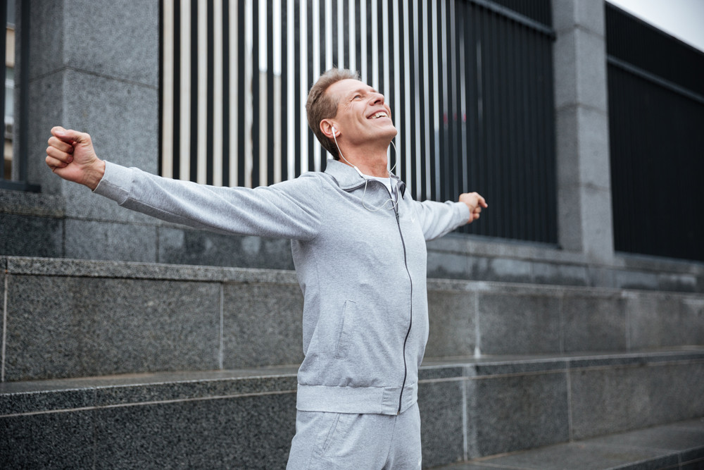 Happy Runner in gray sportswear and headphone warming up on the street with hands to the side. Side view