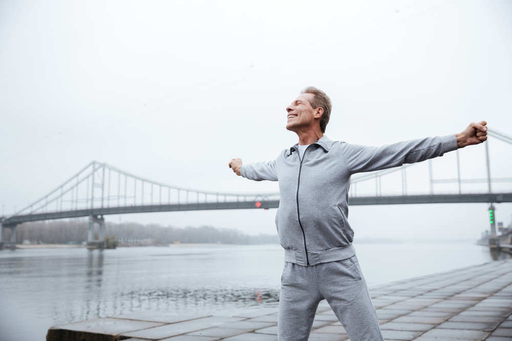 Happy runner in gray sportswear standing near the water with hands to the side