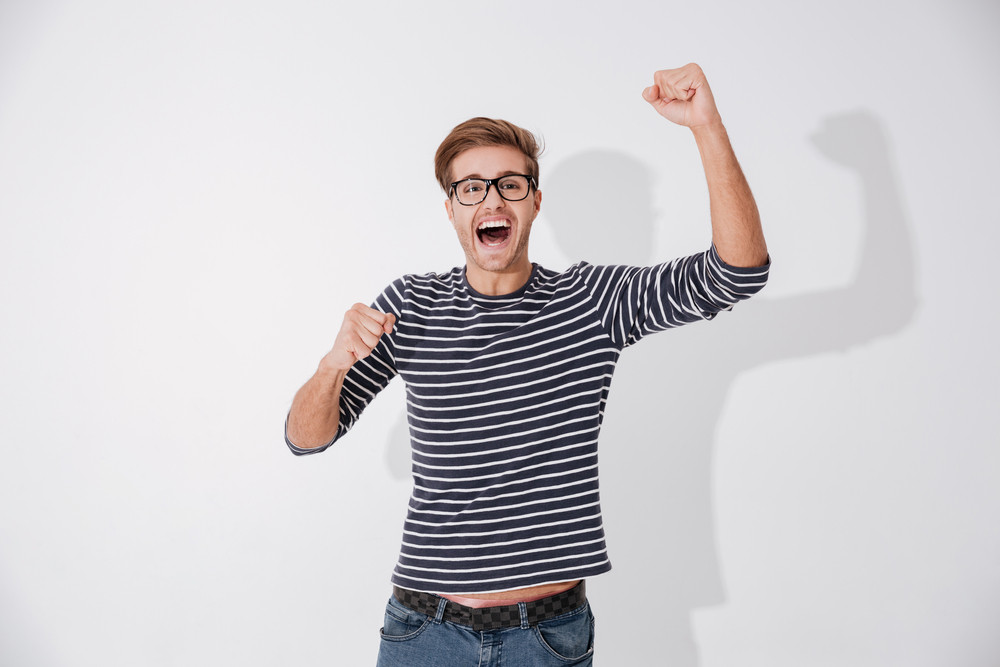 Happy Screaming man in striped sweater and glasses with happy gesture looking at camera. Isolated gray background