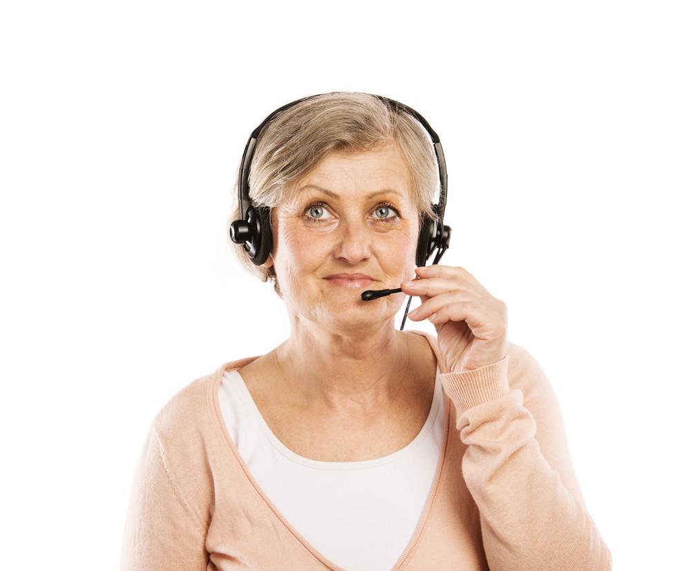 Happy senior woman wearing headset, isolated on white background