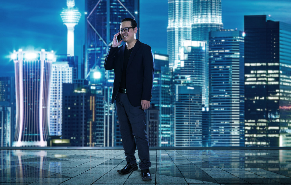 Happy smiling businessman wearing black suit and using modern smartphone near office , successful employer to make a deal while standing near skyscraper office at night.