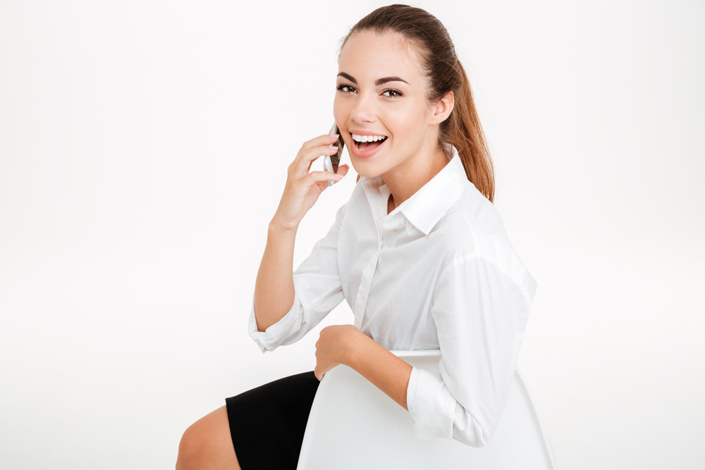 Happy smiling businesswoman talking on the mobile phone while sitting on the chair isolated on a white background