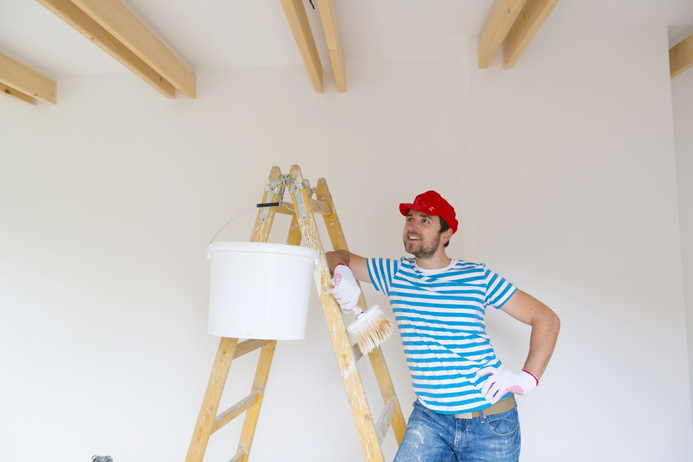 Happy smiling man painting the walls of new home with paintbrush