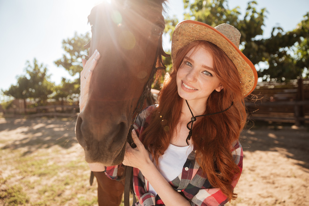 Happy smiling redhead young woman cowgirl with her horse in village
