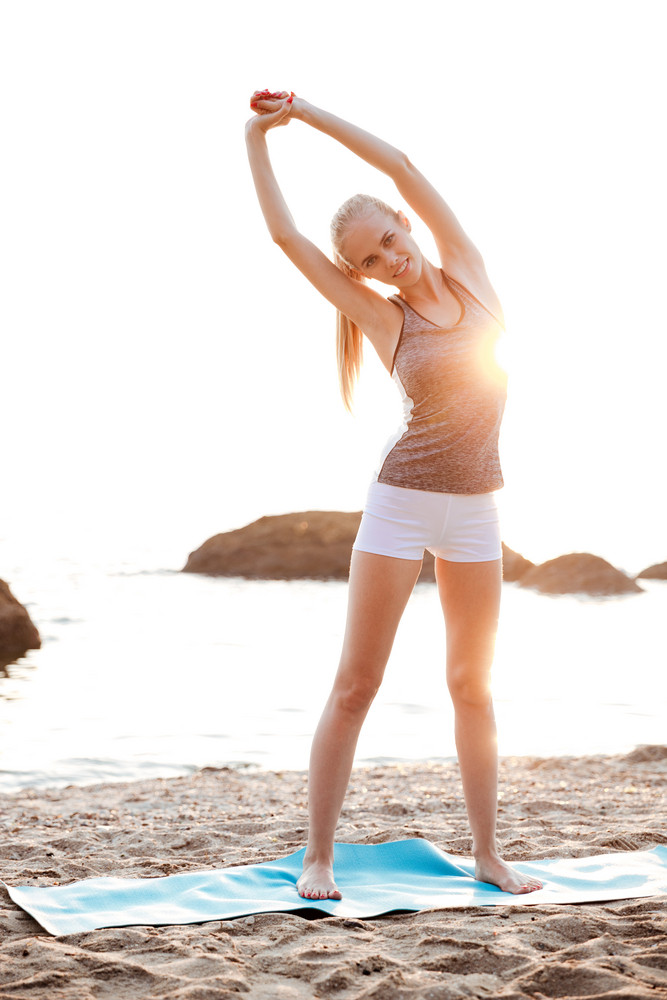 Happy smiling woman doing stretching exercises during yoga on the beach
