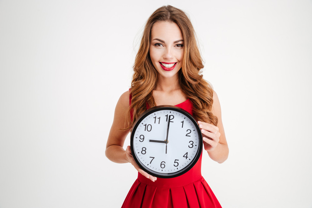 Happy smiling woman in red santa claus dress holding wall clock and looking at camera isolated over white background