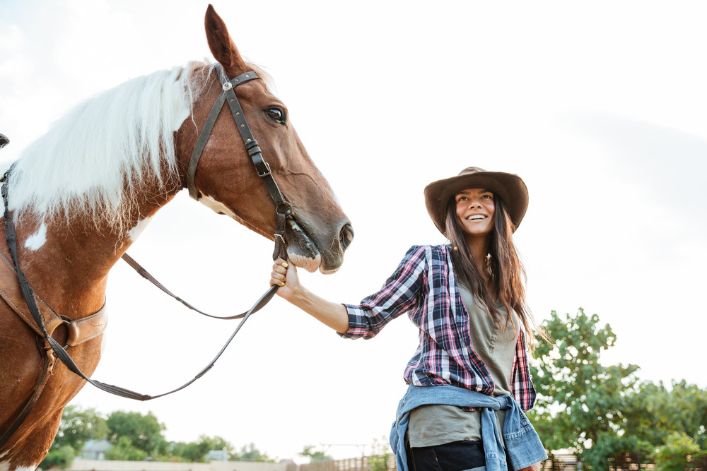 Happy smiling young woman in cowboy hat taking her horse for a walk at the farm