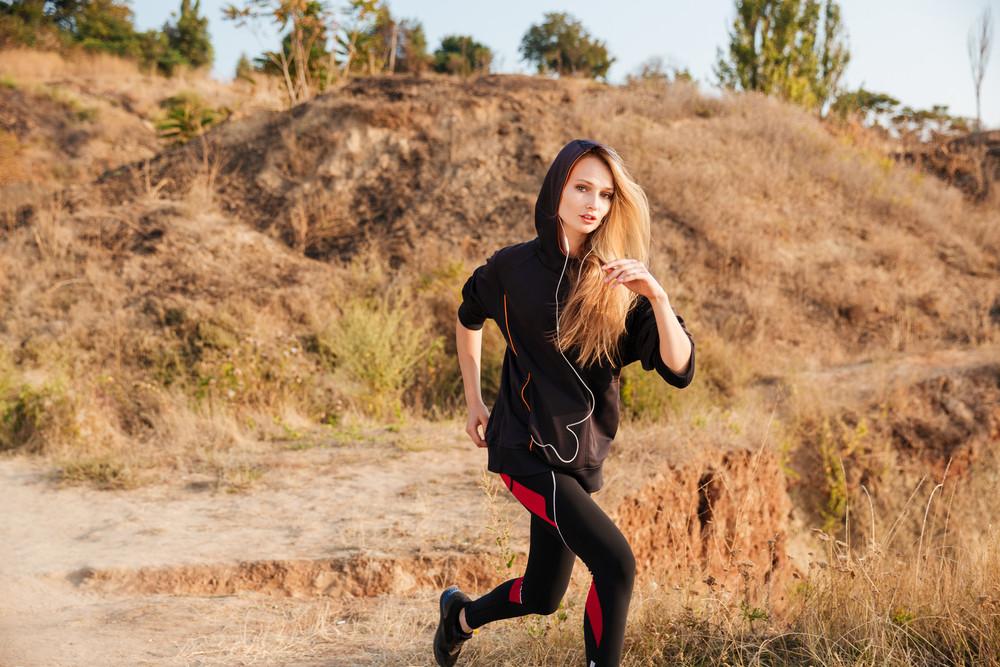 Happy sporty woman in earphones and hoodie running outdoors