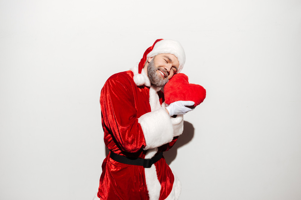 Happy tender man santa claus standing and holding red heart