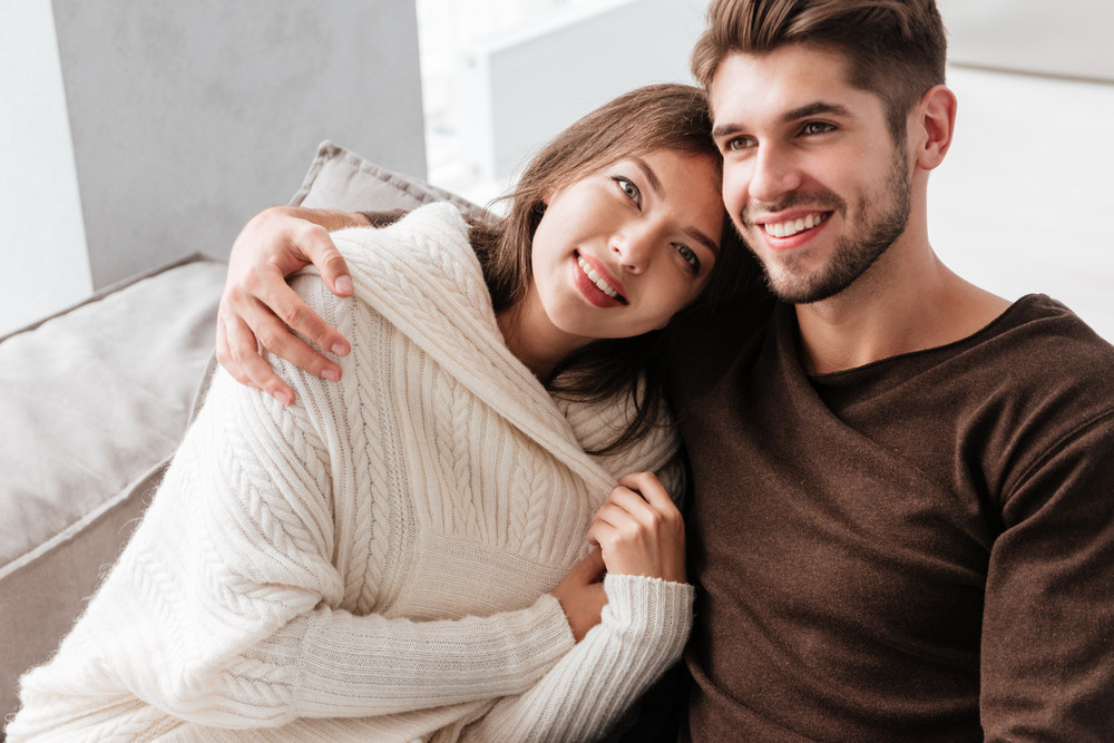 Happy tender young couple sitting and hugging on sofa at home
