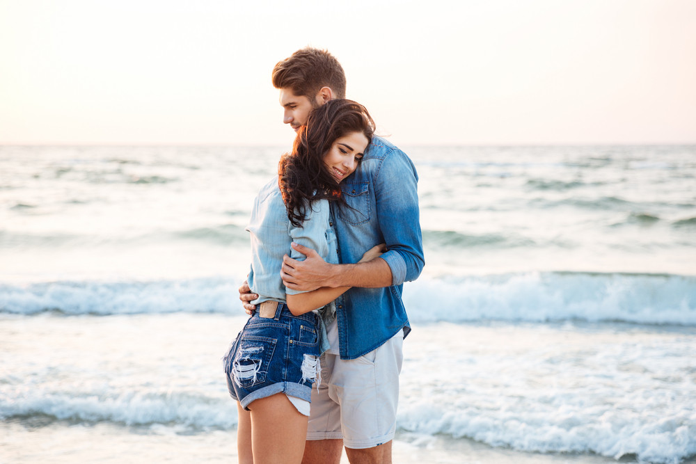 Happy tender young couple standing and hugging on the beach
