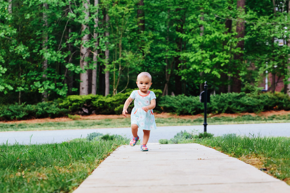 Happy toddler girl walking in front of her house