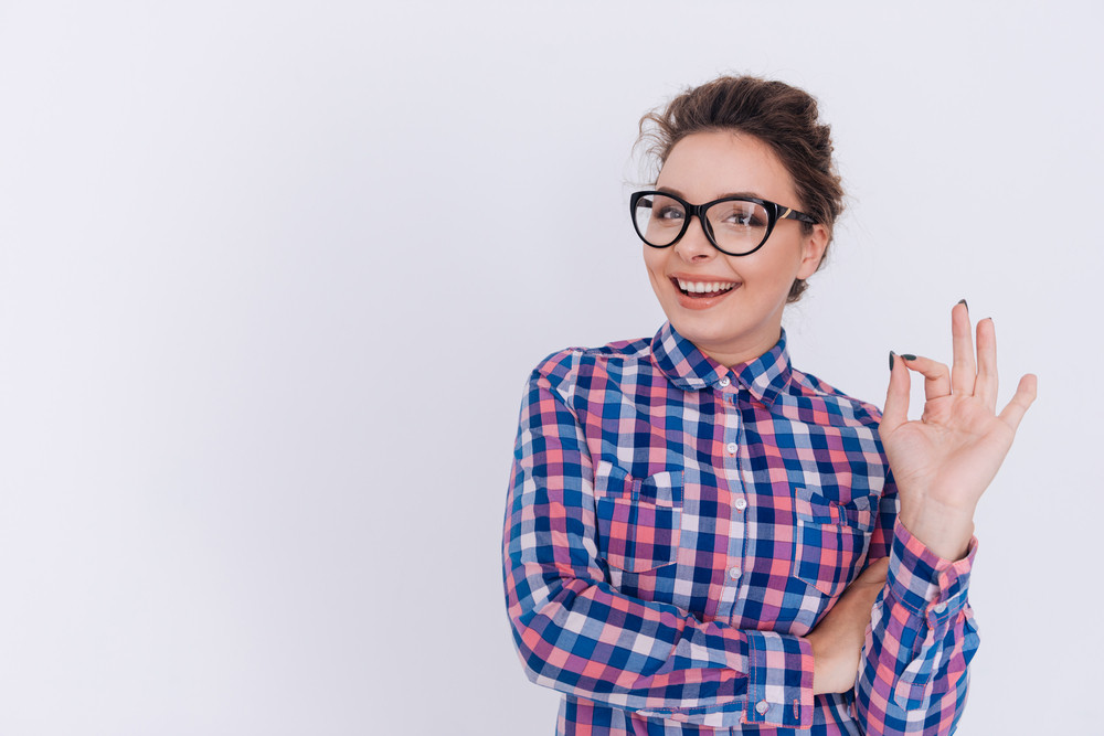 Happy Woman in glasses and checkered shirt showing ok sign and looking at camera