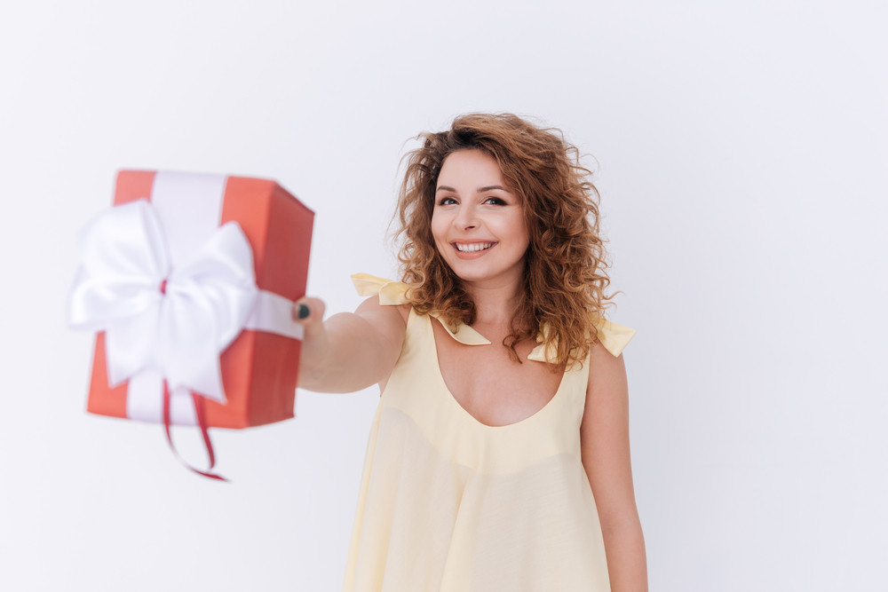 Happy woman in singlet showing gift at camera. Isolated gray background