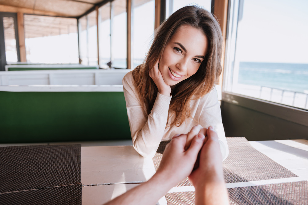 Happy woman sitting by the table on date and holding hand her man in cafe near the sea. First- person view