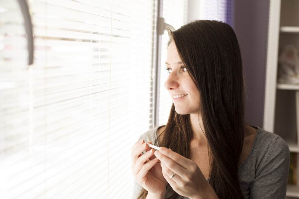 Happy woman with positive pregnancy test result. She is excited at home.