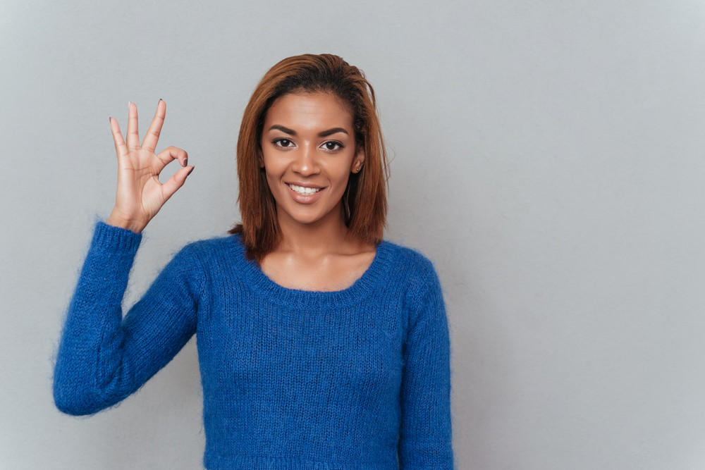 Happy young african woman in sweater showing ok sign and looking at camera. Isolated gray background