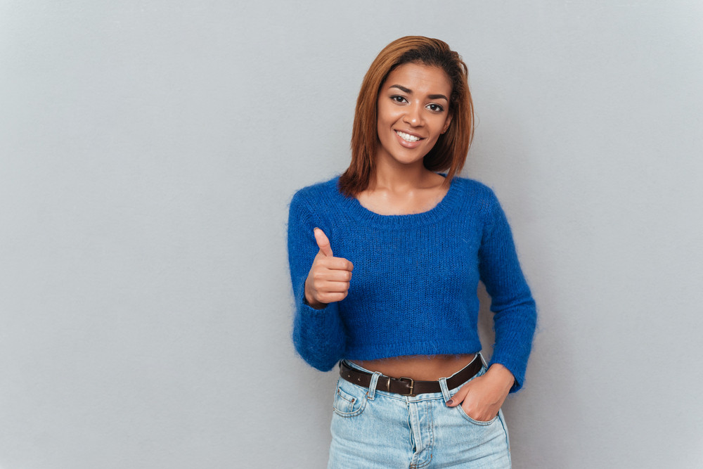 Happy young african woman in sweater showing thumb up and second hand holding in pocket. Isolated gray background