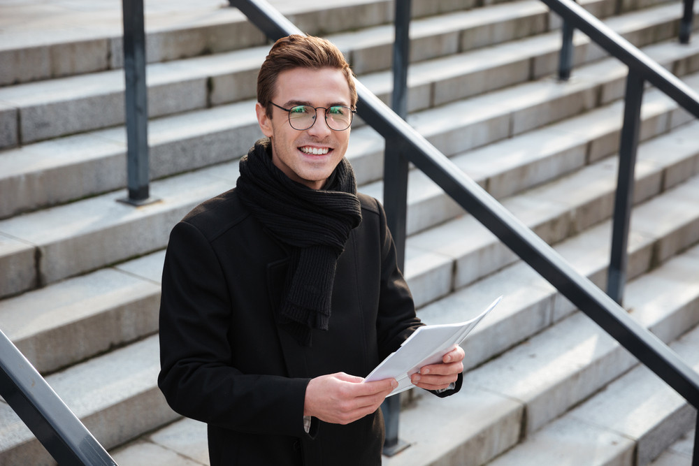 Happy young business man in glasses and warm clothes with documents standing on the stairs and looking at camera