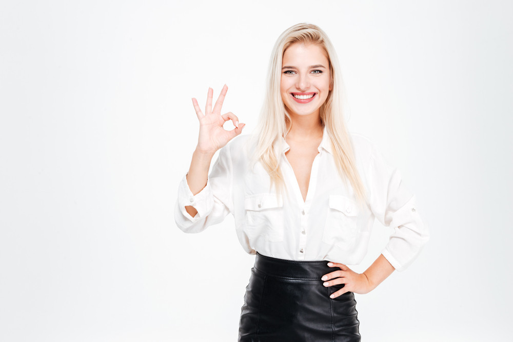 Happy young businesswoman showing ok sign isolated on a white background