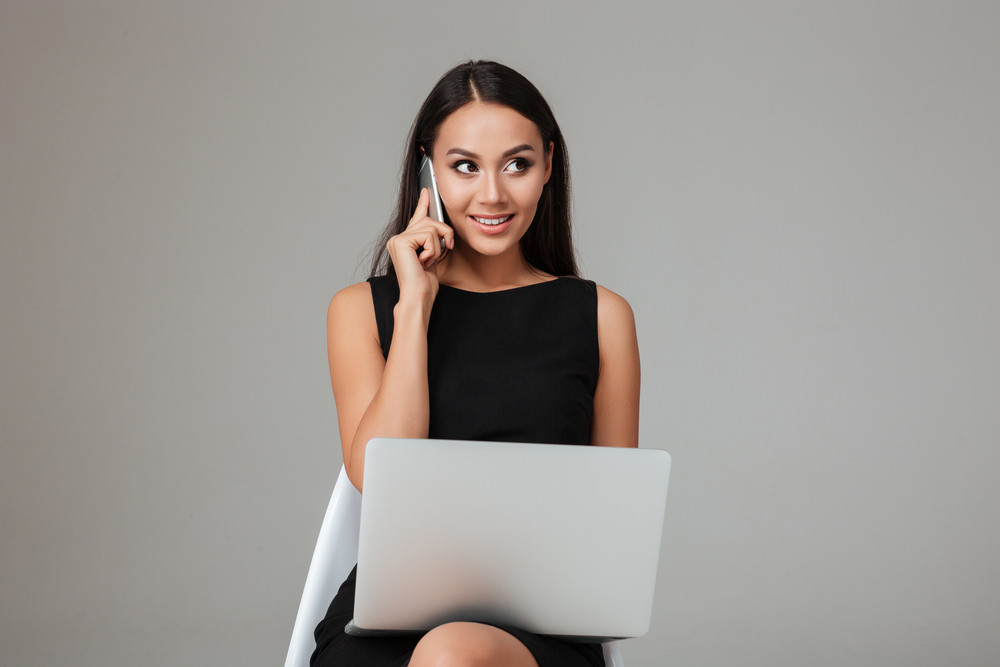 Happy young businesswoman sitting on the chair with laptop and talking on mobile phone over gray background