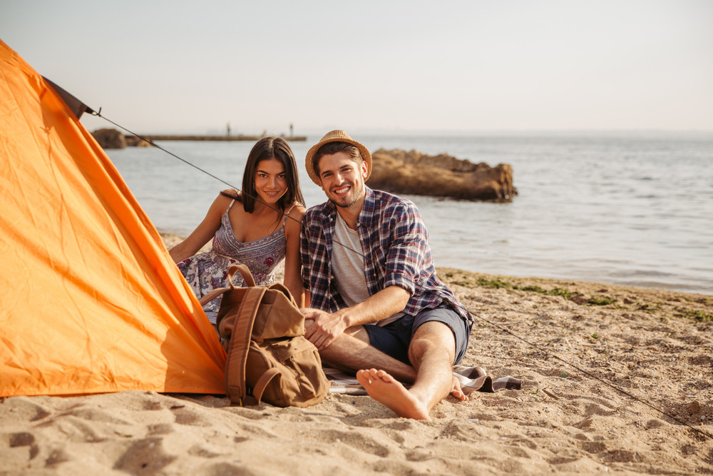 Happy young cheerful couple having fun camping at the beach