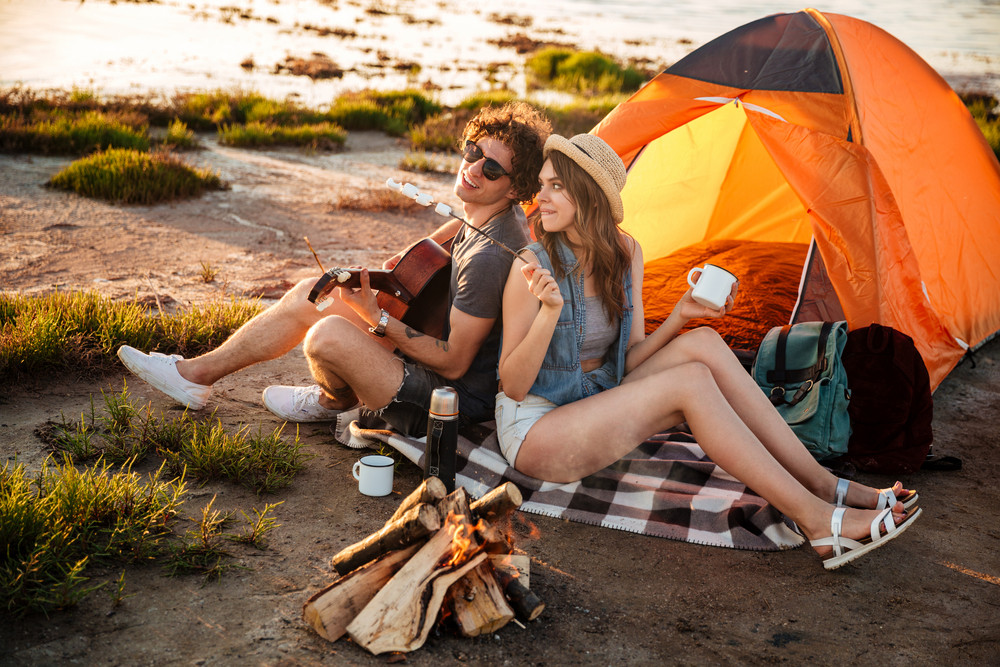 Happy young cheerful couple in love having fun camping at the beach