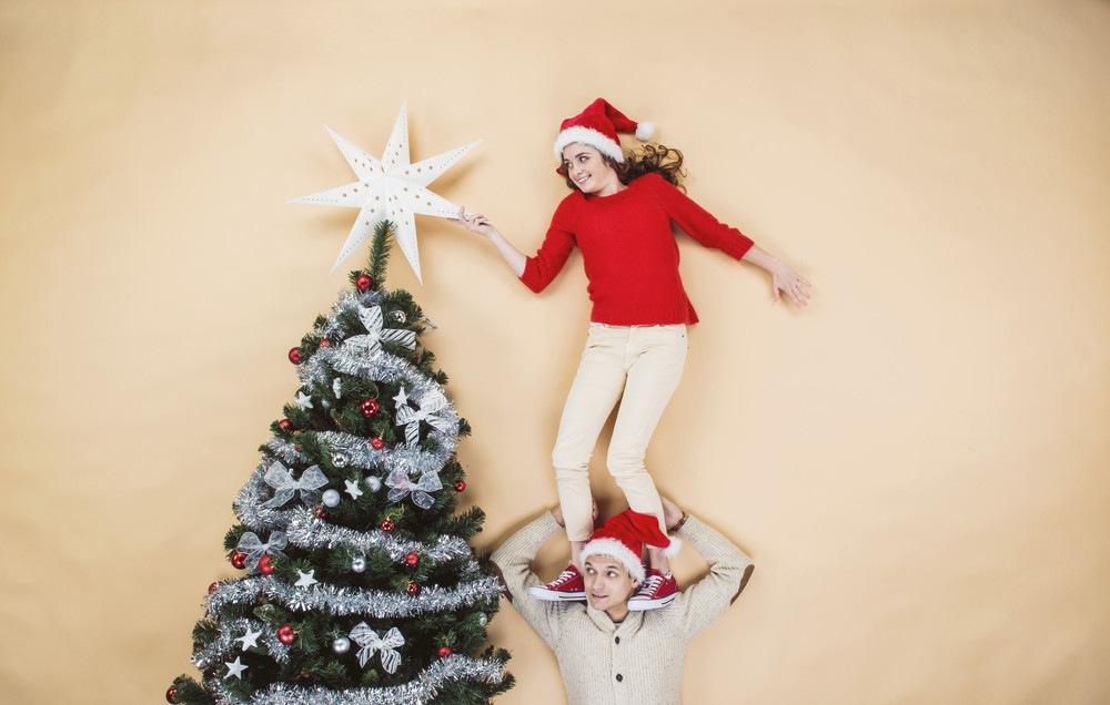 Happy young couple decorating Christmas tree against the beige background