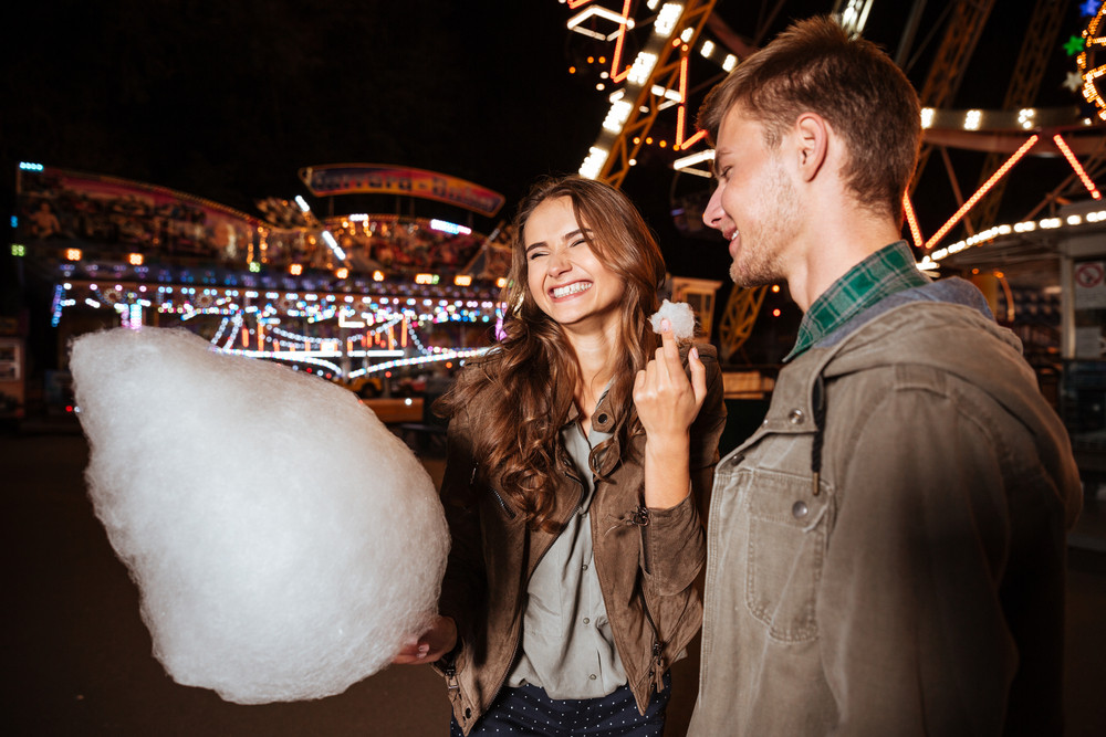 Happy young couple eating cotton candy and laughing in amusement park