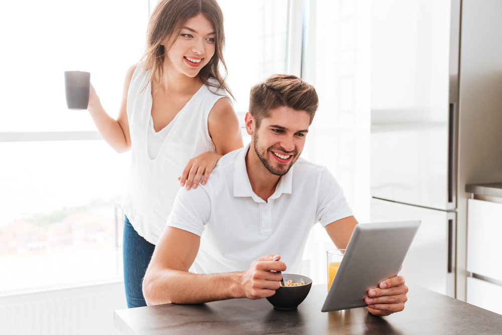 Happy young couple having breakfast and using tablet on the kitchen