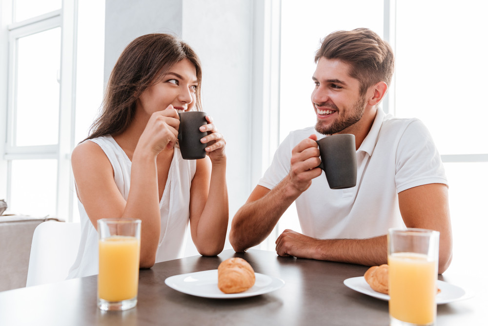 Happy young couple having breakfast on the kitchen together