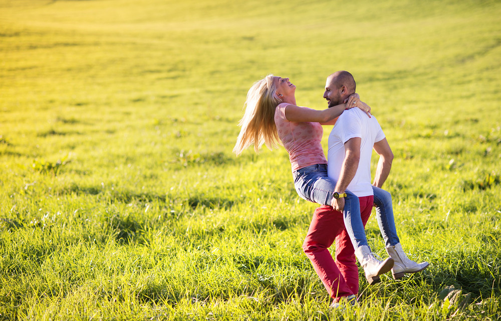 Happy young couple having fun outside on a meadow