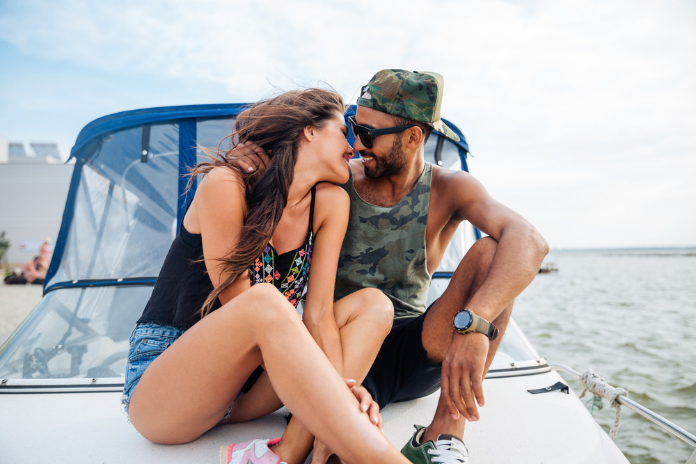Happy young couple hugging and kissing on boat