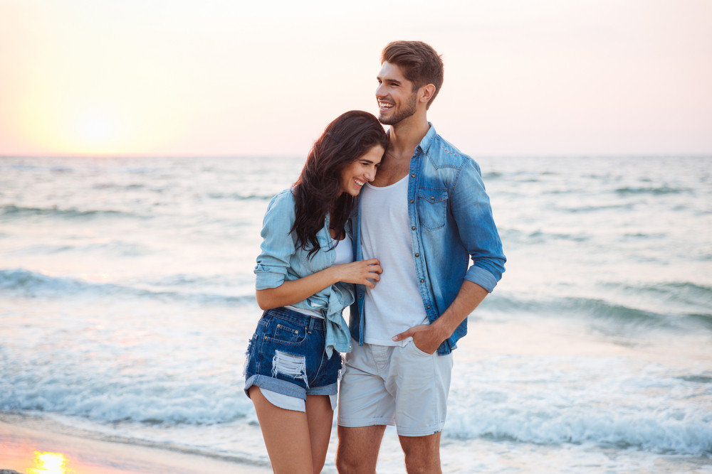 Happy young couple hugging and laughing on the beach