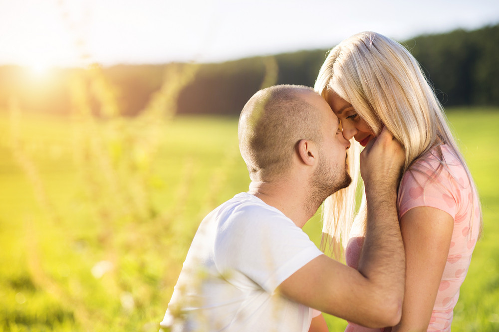 Happy young couple in love hugging and kissing outside in a park