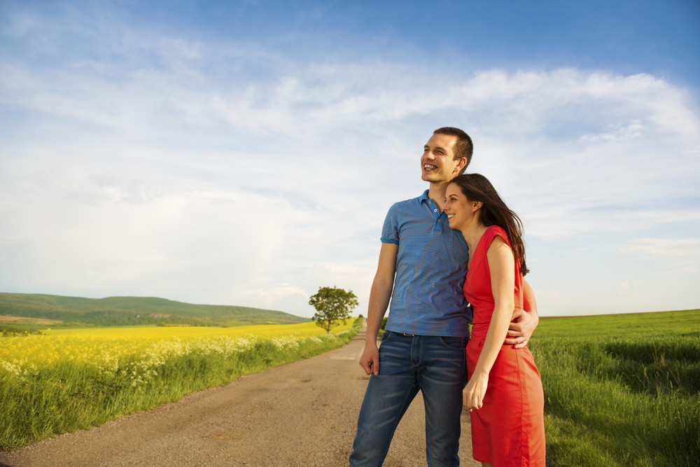 Happy young couple in love hugging on countryside road next to the colza field