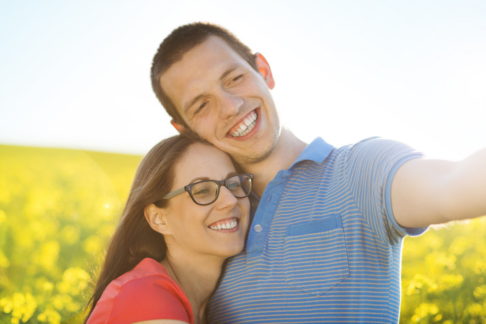 Happy young couple in love with heart shaped baloon in yellow colza field