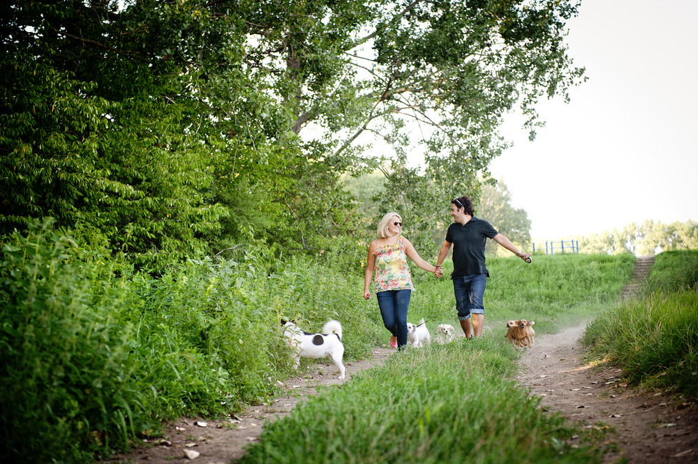 Happy young couple is walking their two dogs in green nature