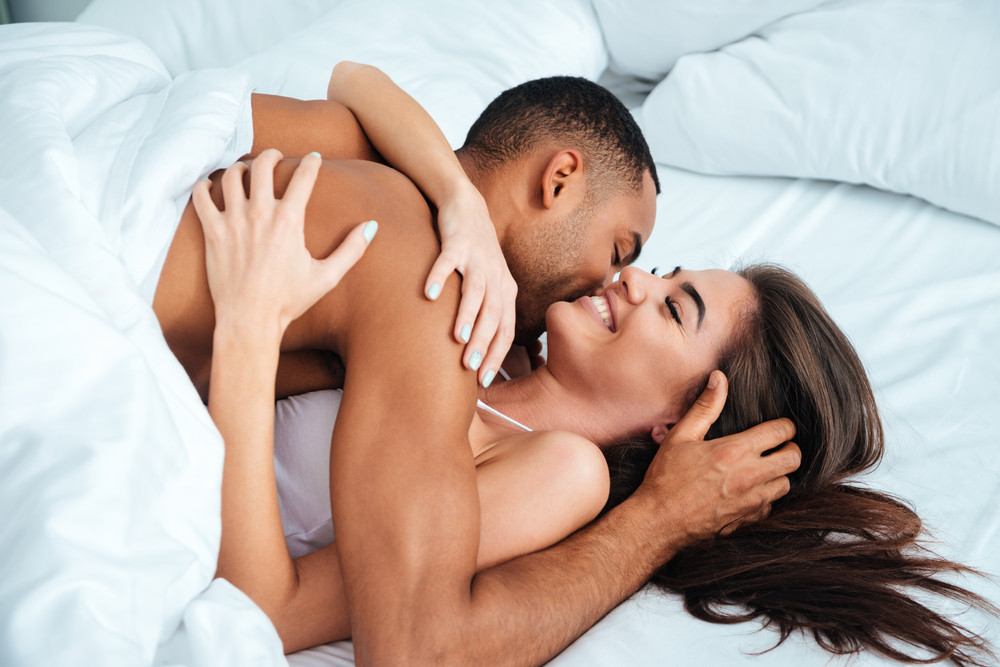 Happy young couple laughing and kissing in bed at home