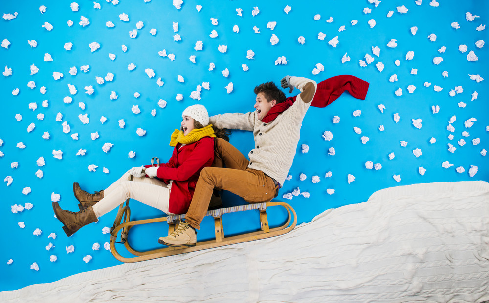 Happy young couple on sledge having fun against the blue background with snowflakes