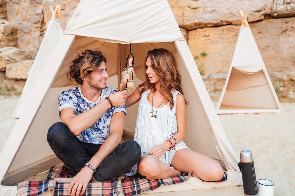 Happy young couple sitting and smiling in wigwam on the beach
