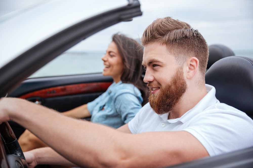 Happy young couple smiling while sitting inside of their convertible