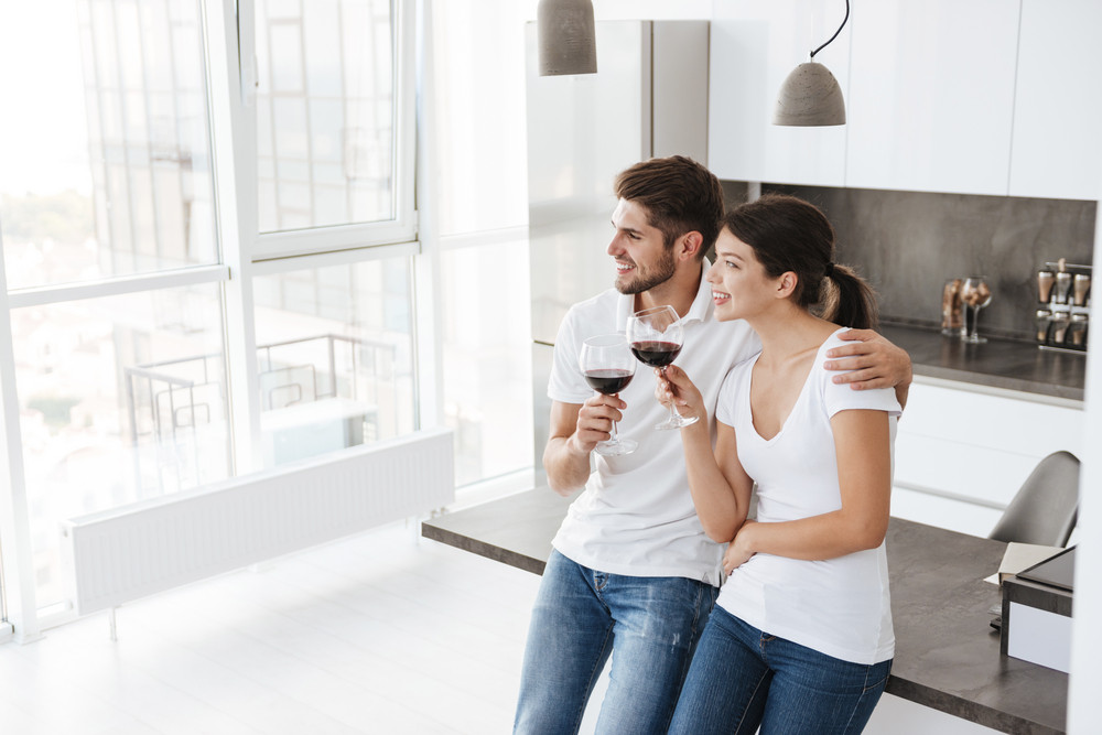 Happy young couple standing and drinking red wine on the kitchen