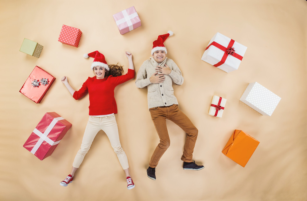 Happy young couple with Christmas presents jumping against the beige background