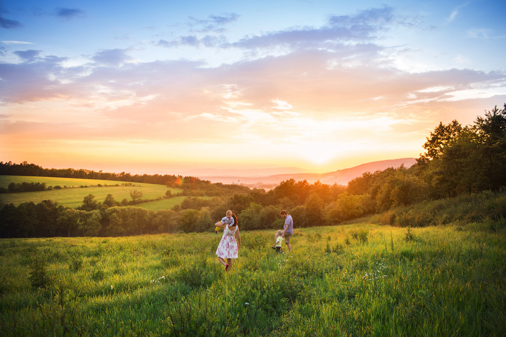 Happy young family have fun together in nature in sunset field