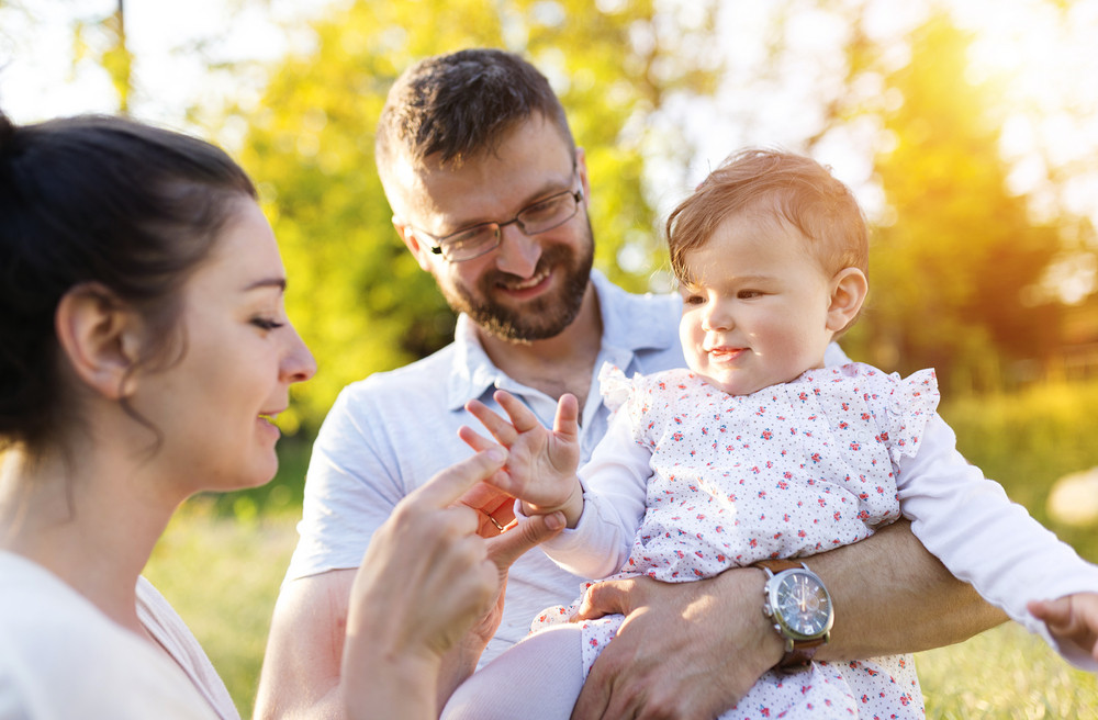 Happy young family having fun outside in spring nature