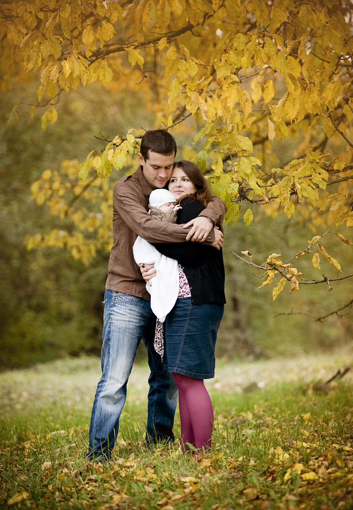 Happy young family relaxing together in autum nature