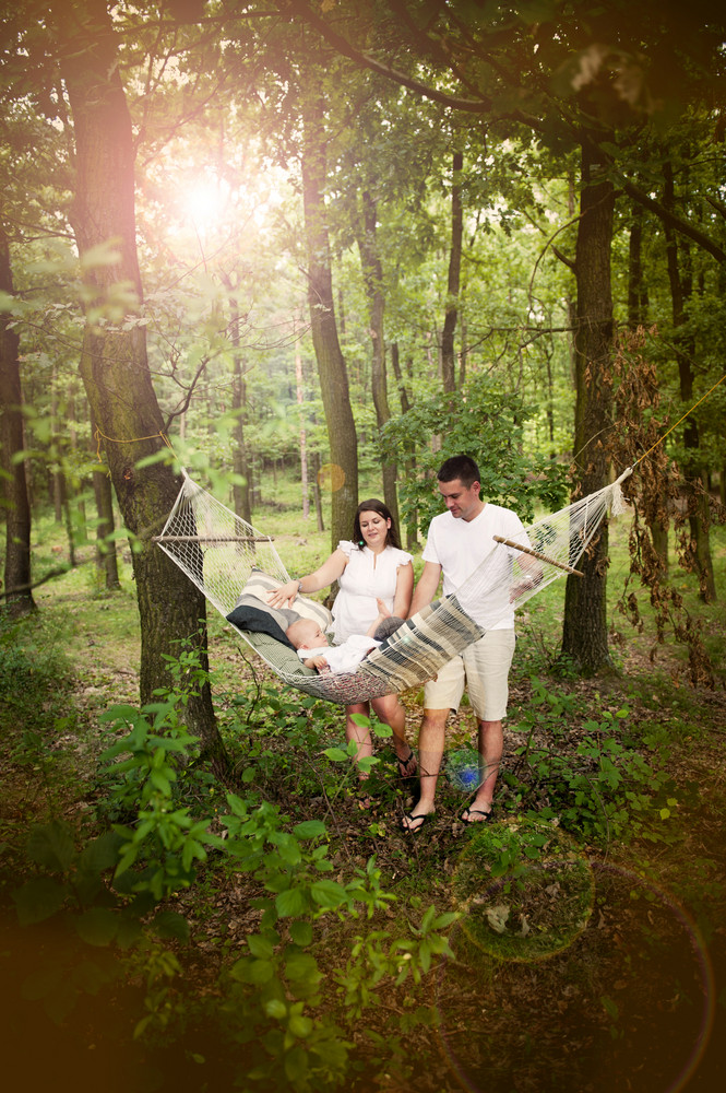 Happy young family spending time together in green nature, little boy is lying in hammock