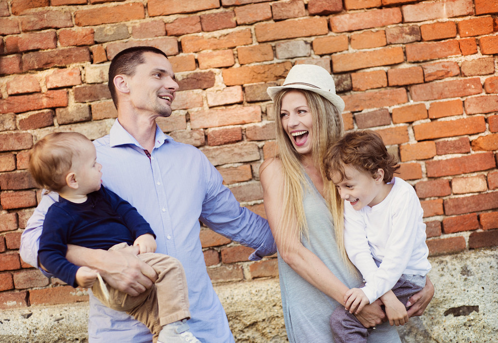 Happy young family spending time together outside by the brick wall.