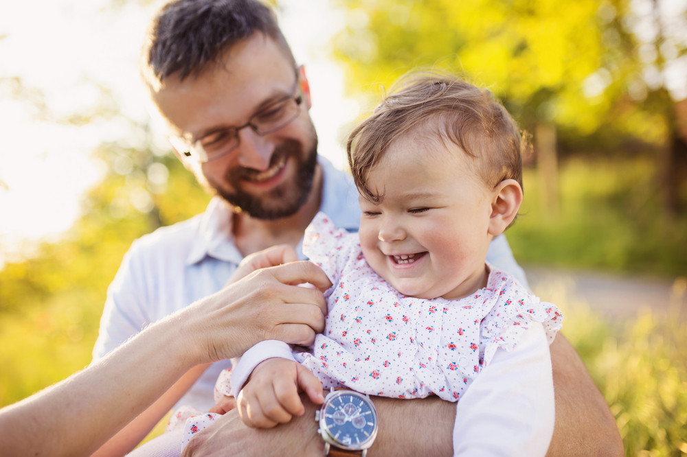 Happy young father and daughter having fun outside in spring nature